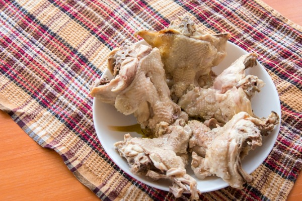 boiled-chicken-backs-in-the-plate-on-the-wooden-table-top-on-a-picture-id838459138